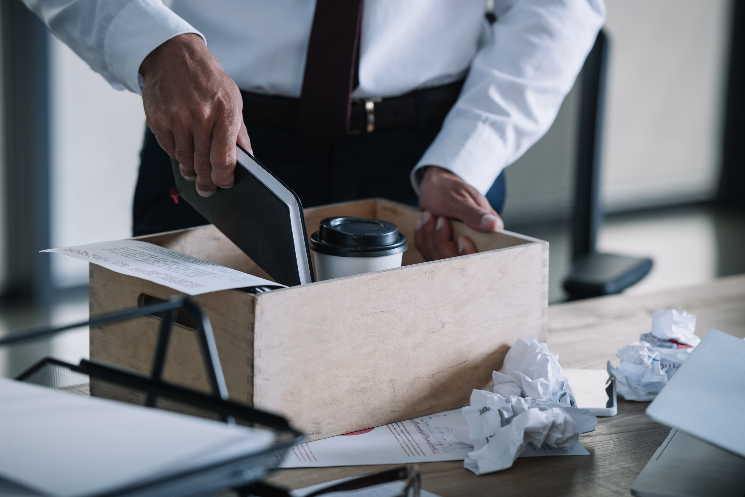 cropped view of man putting notebook in wooden box near paper cup and crumpled paper balls on table